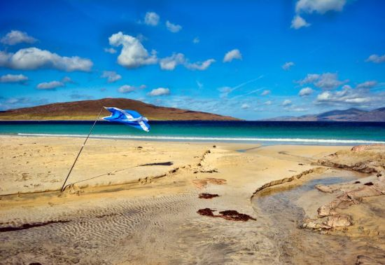 Panorama of a beach under a bright blue sky; a saltire on a flagpole is flapping in the wind.