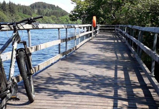 View of a boardwalk overlooking a loch; a mountain bike rests against the railings