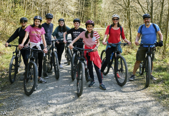 Group of 8 people on mountain bikes smiling at the camera