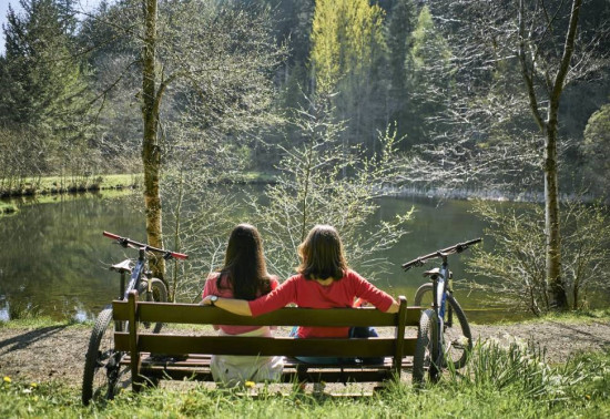 Two women with bikes looking at a pond
