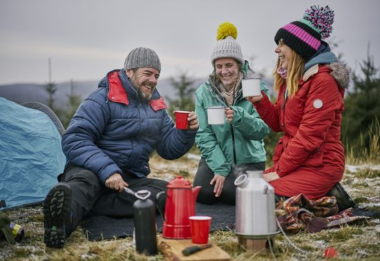 A man and two women drinking from mugs while sat around a campstove