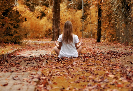 Woman in lotus position facing away from camera. Brown, autumnal leaves are scattered on the ground.