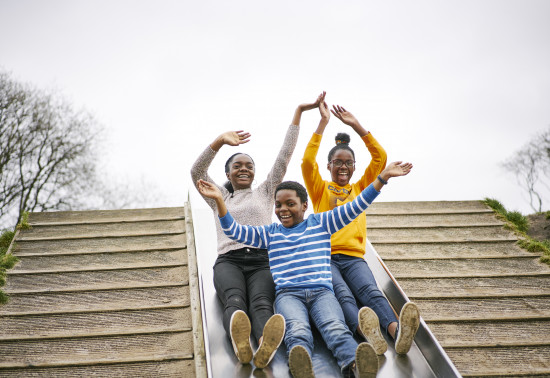 Three children going down a slide, side by side