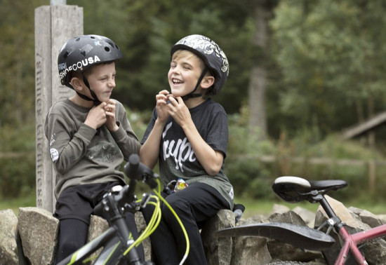 Two wee boys putting their bike helmets on