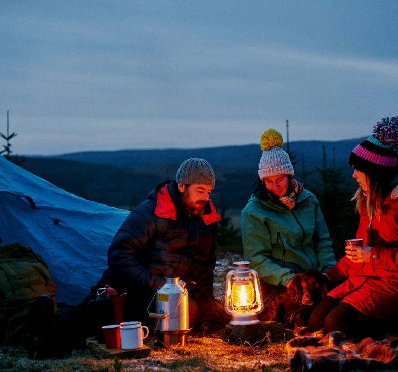 Three people gathered around a camping stove at dusk