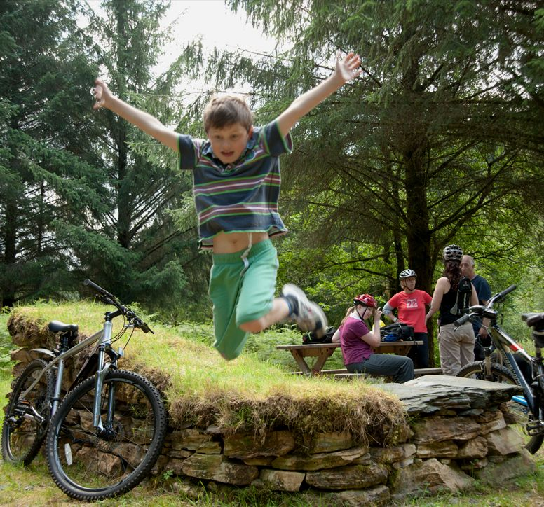 A boy jumping off a grassy perch. His family and their bikes in the background