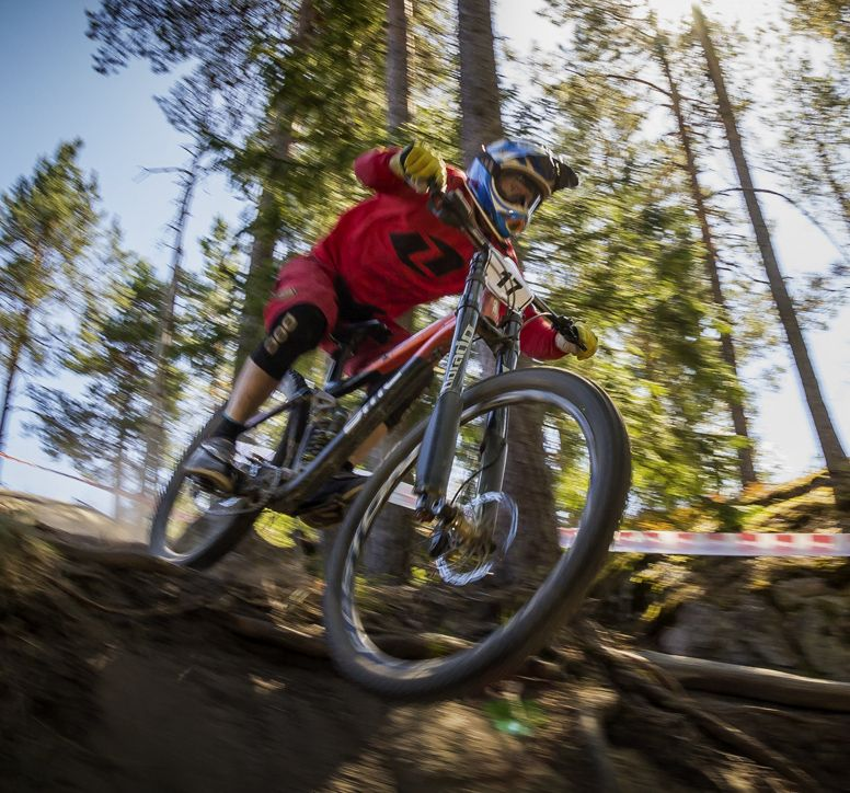 Mountan biker riding down a forested slope