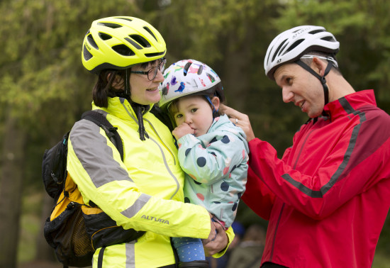 Family with young child and all wearing cycling helmets