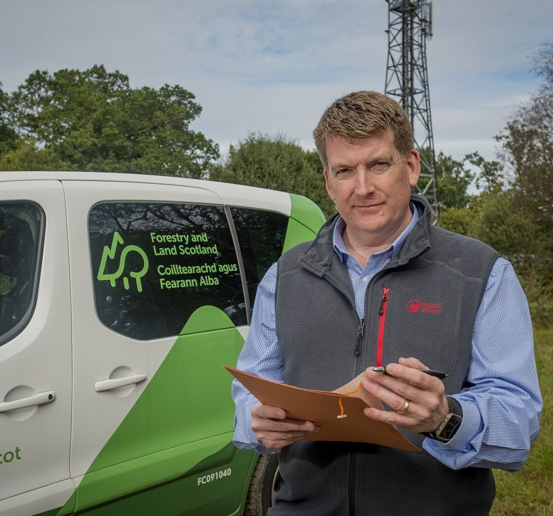 Man standing next to a Forestry & Land Scotland van