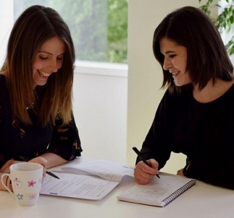 Two women writing at a desk