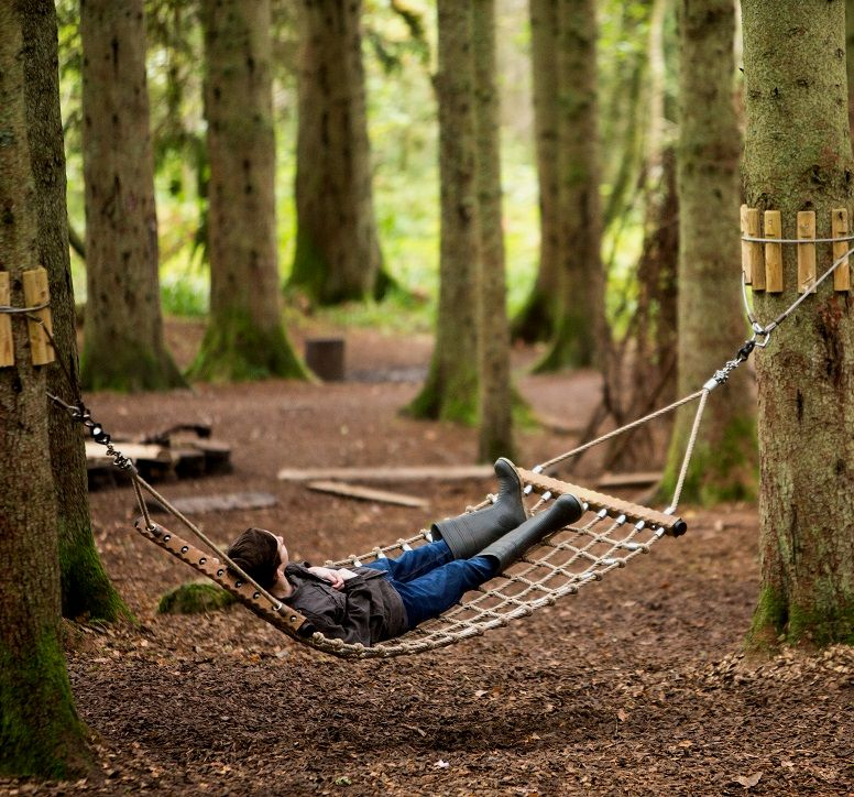 A boy resting in a hammock between two trees at The Lodge Visitor Centre