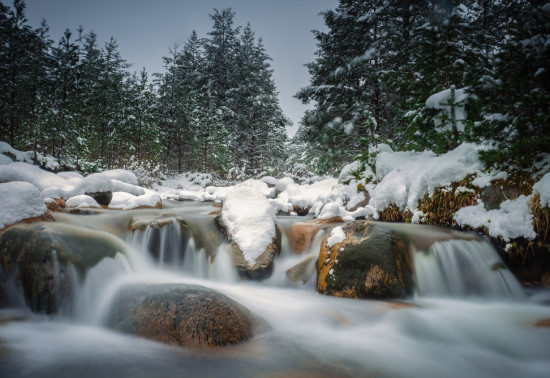 Snow covered rocks in a fast flowing river