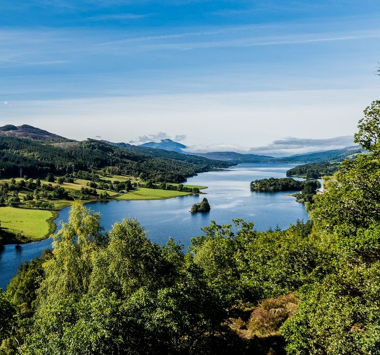 Bright blue loch and lush tree-covered hills, as seen from Queen's View Visitor Centre