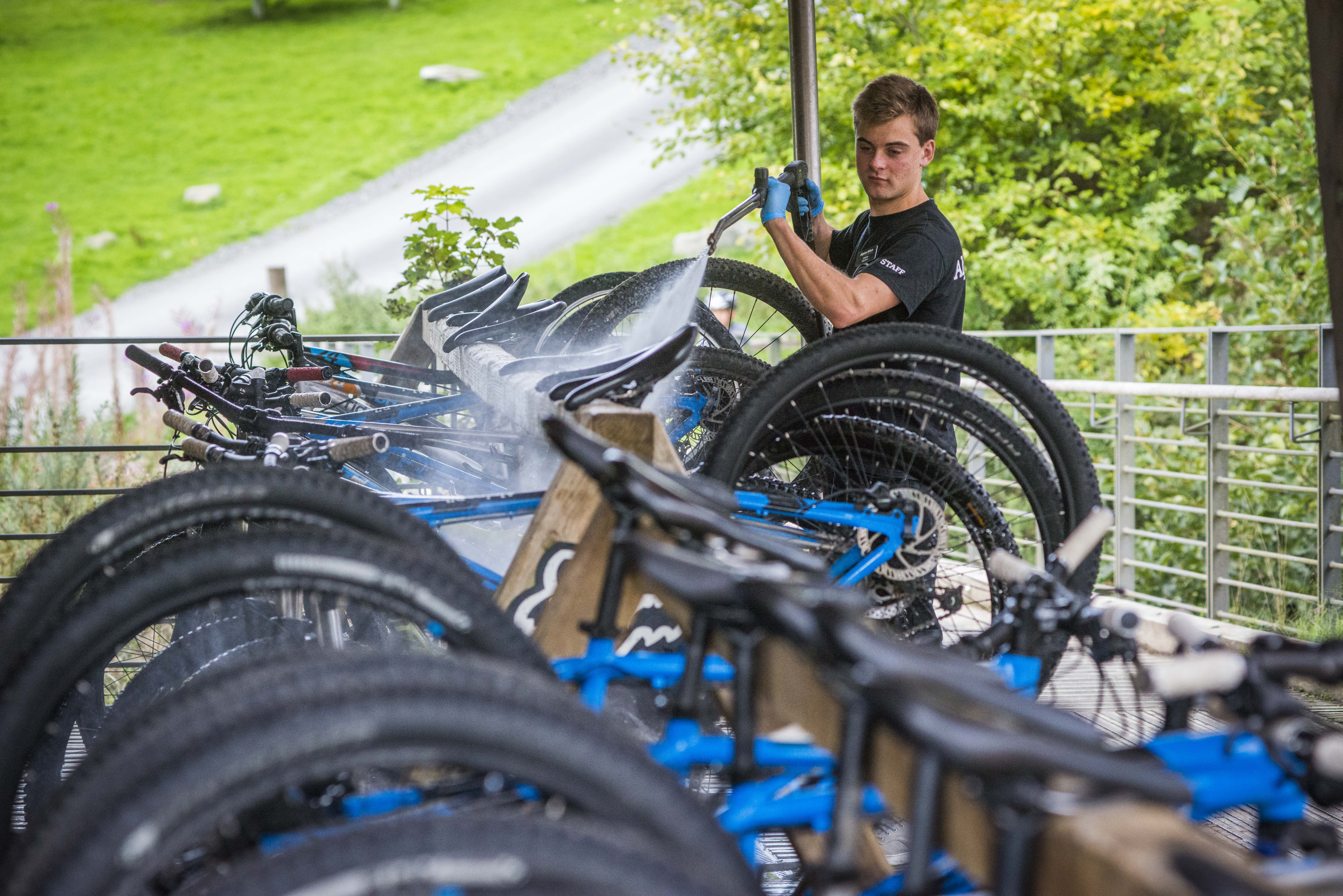 A man uses a pressure washer to clean bikes at Glentress