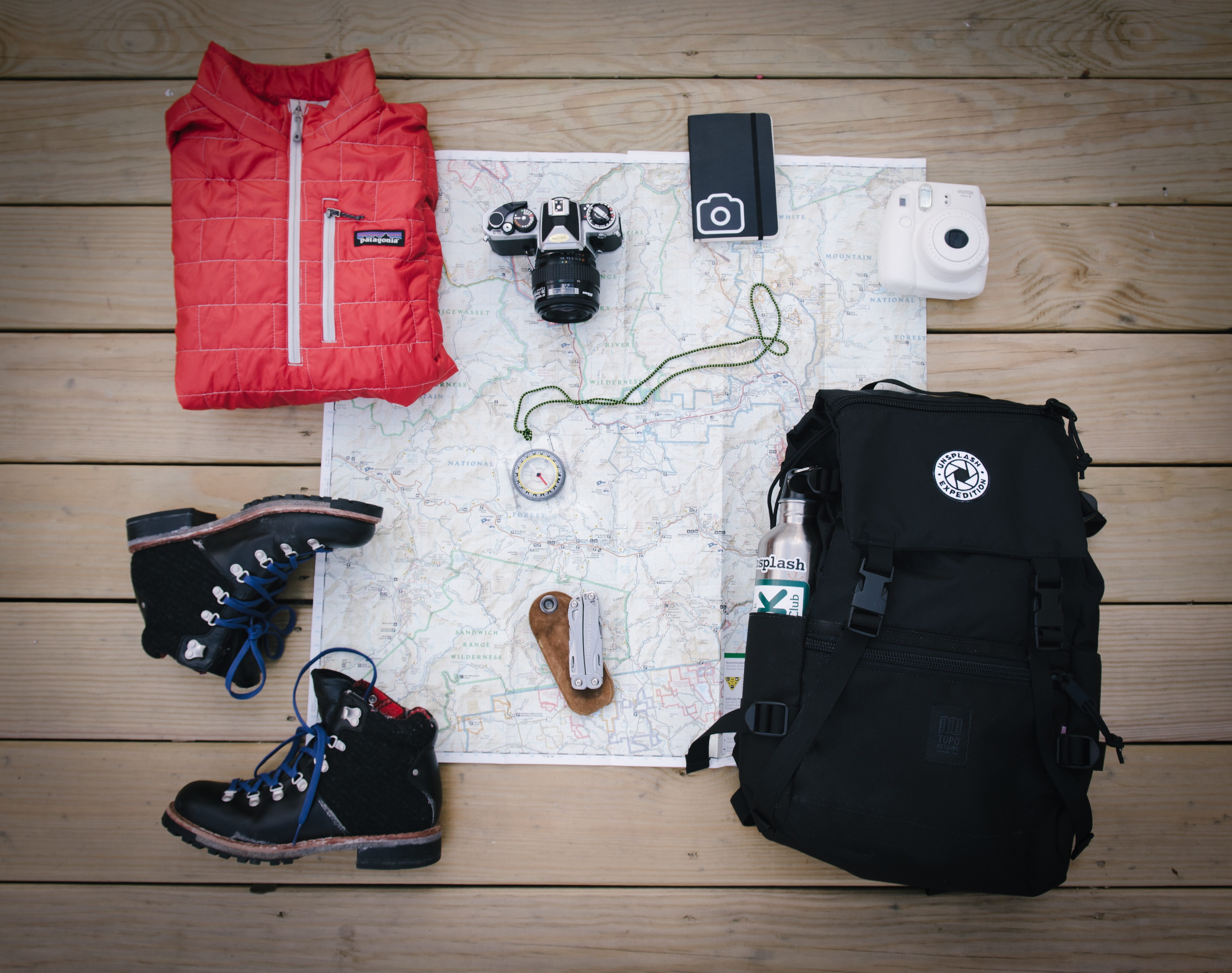 Camping gear including boots, rucksack, compass, map and gilet