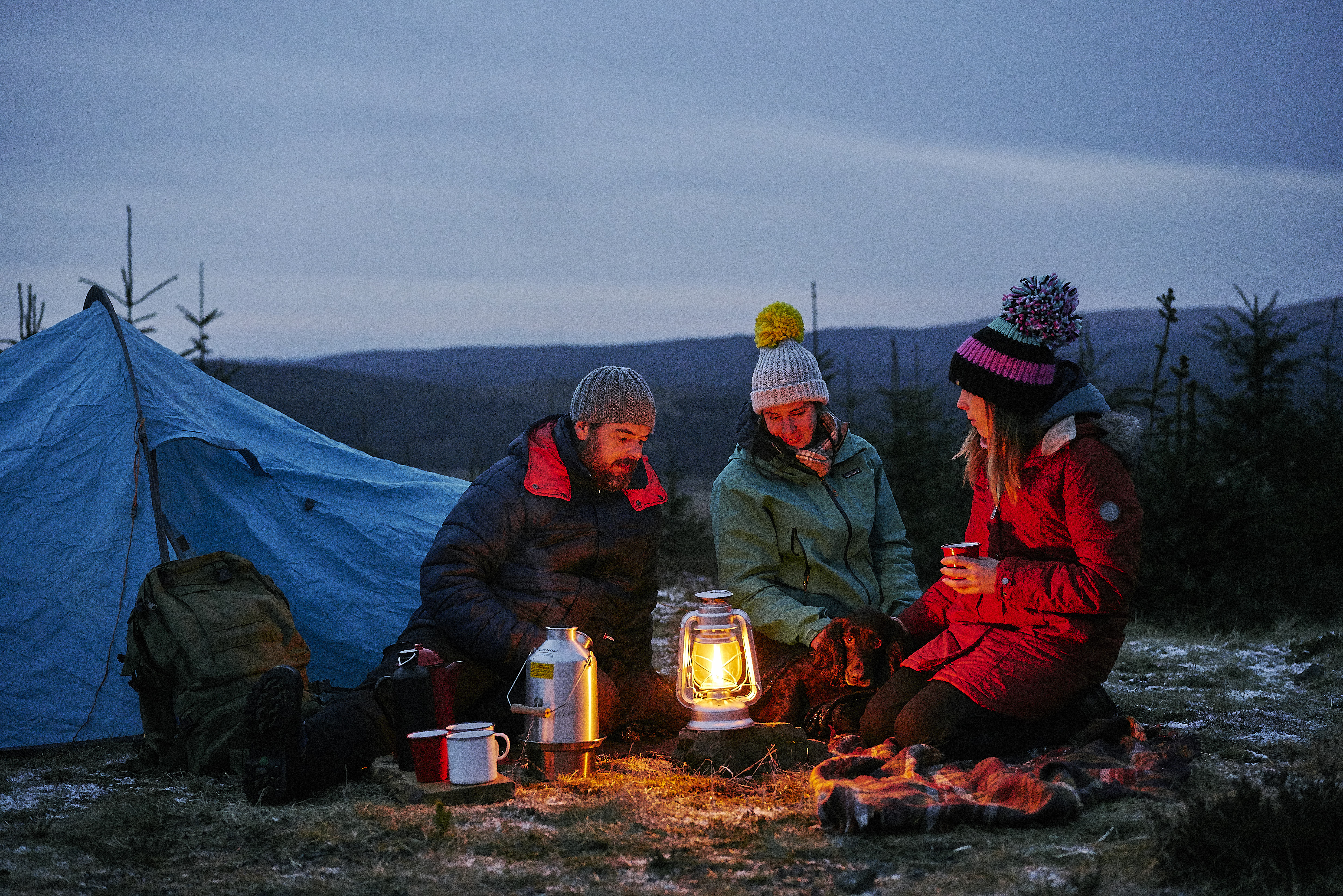 Three friends camping under the night sky
