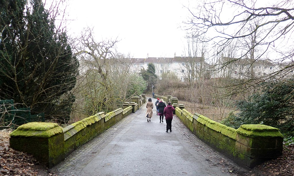 A well-surfaced pedestrian bridge leading towards a housing estate