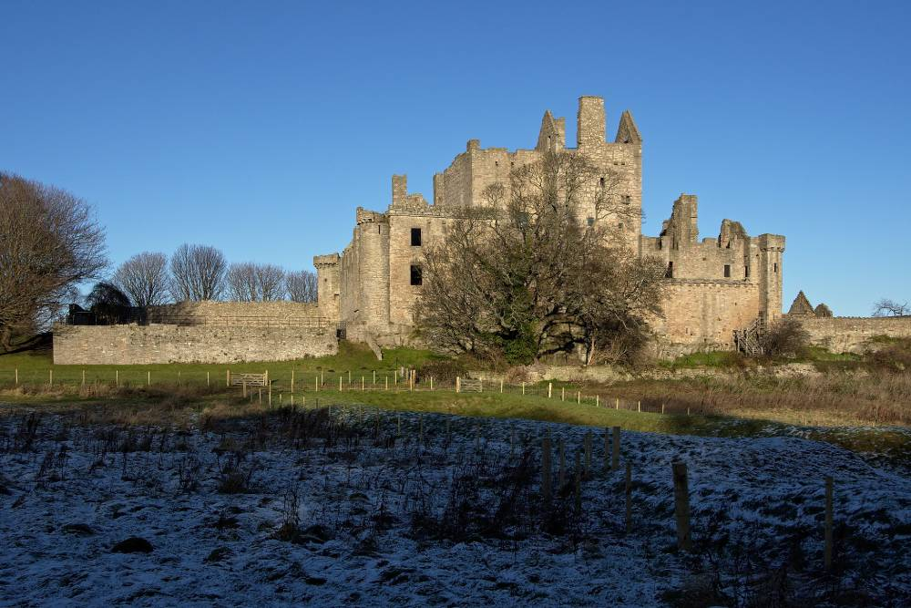 Castle basking in blue sky and sunshine, with a shadowed and frosty field in the foreground