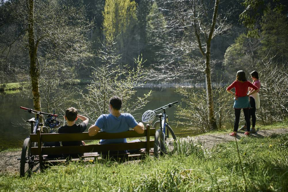 Two people sitting on a bench with bikes to either side looking out at a small pond