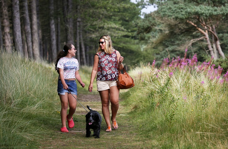 Two women in summer clothing walking a black dog along a small track in a forest