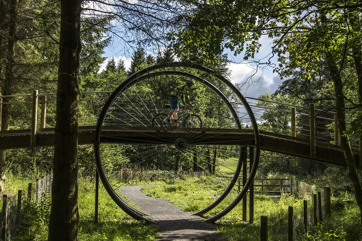 Man on mountain bike crossing distinctive wooden bridge in style of a spokes wheel, over a forest path, surrounded by green trees