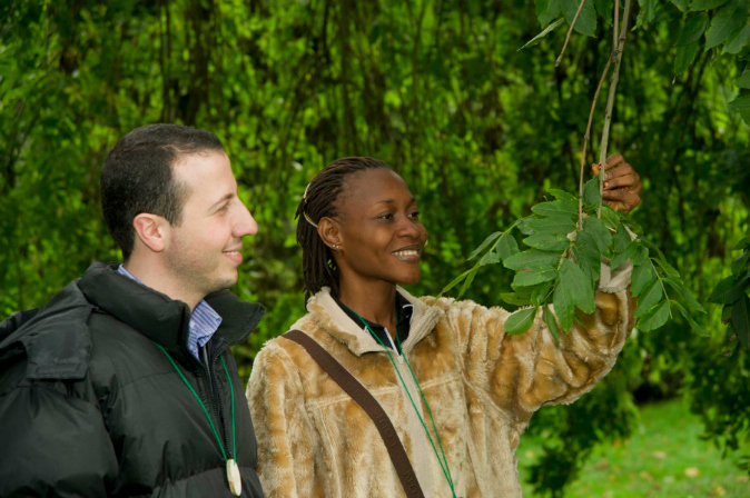 Man and woman smiling while inspecting the leaf on a tree