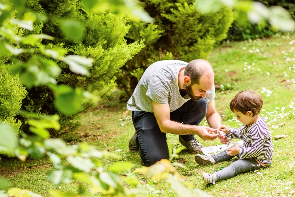 Man and child sitting on trimmer grass next to trees, examining something