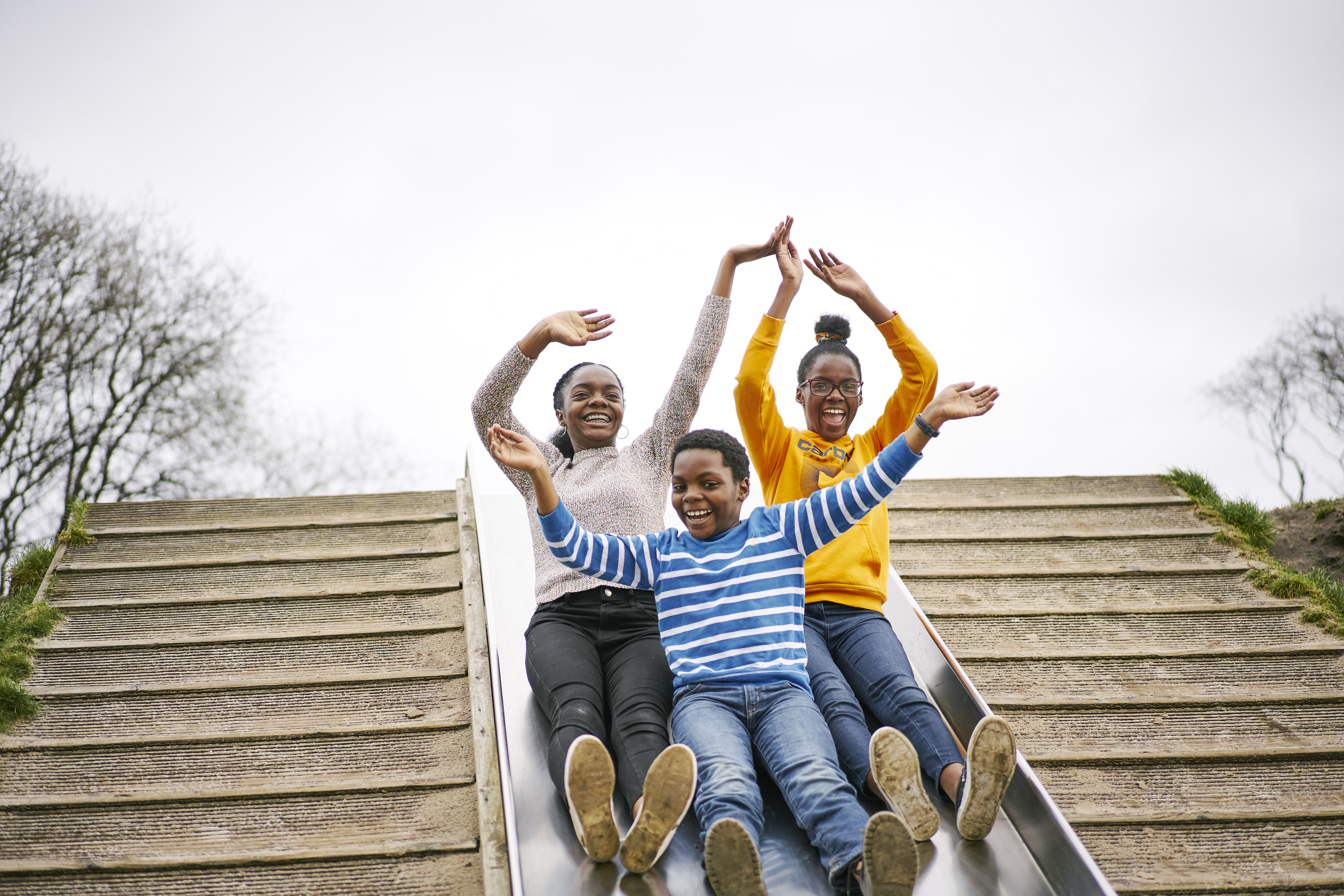Three children going down a large playpark slide