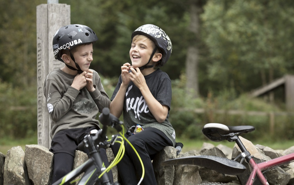 Two boys sitting on a stone wall buckling on cycle helmets with their bikes in front of them