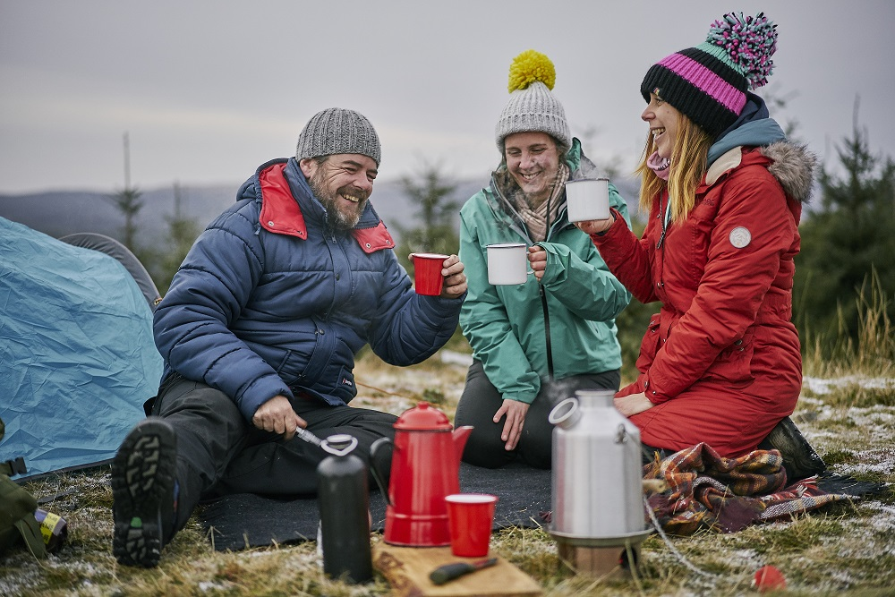 Three people wrapped up in hats and warm clothes drinking hot beverages outside, with a tent beside them