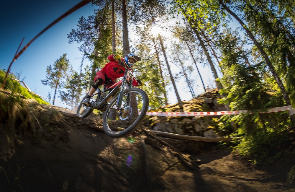 Person mountain biking in a forest under blue skies, jumping of a drop