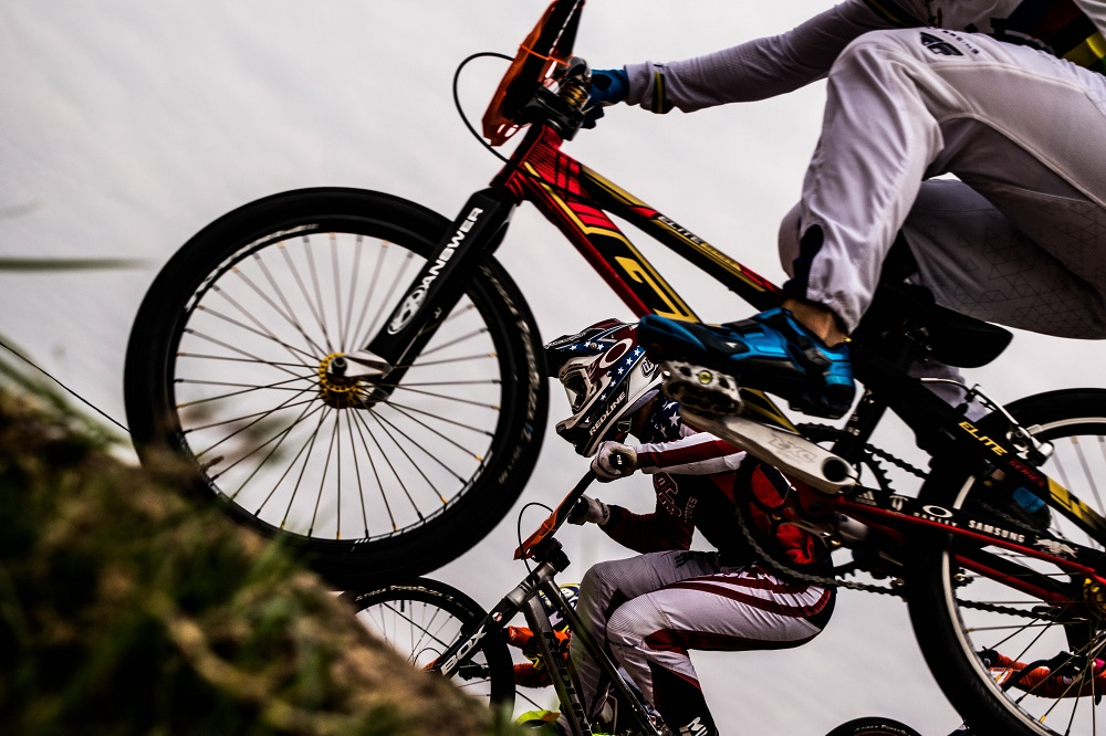 Close up of two people racing BMX bikes