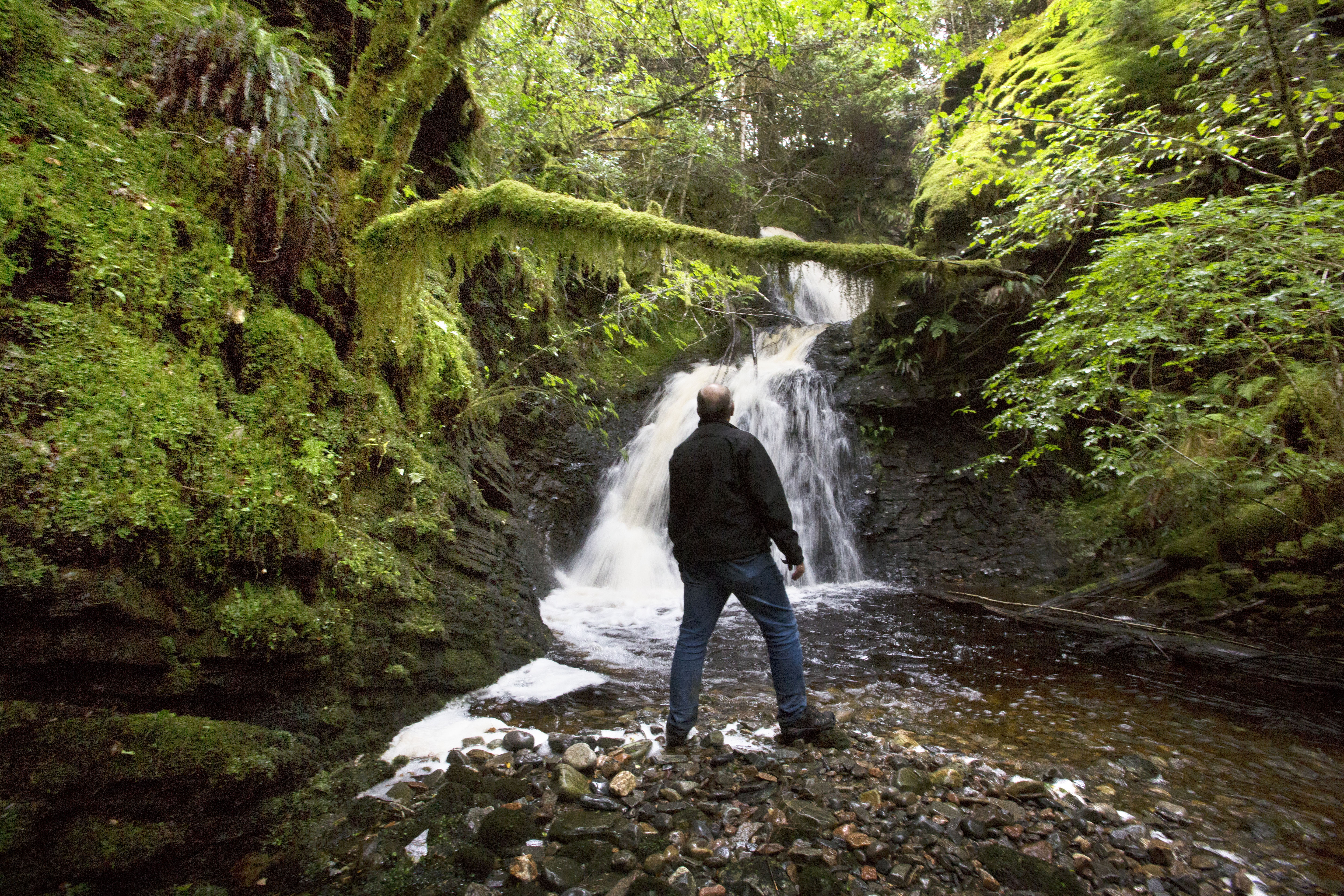 Man standing in front of waterfall at Allt na Criche