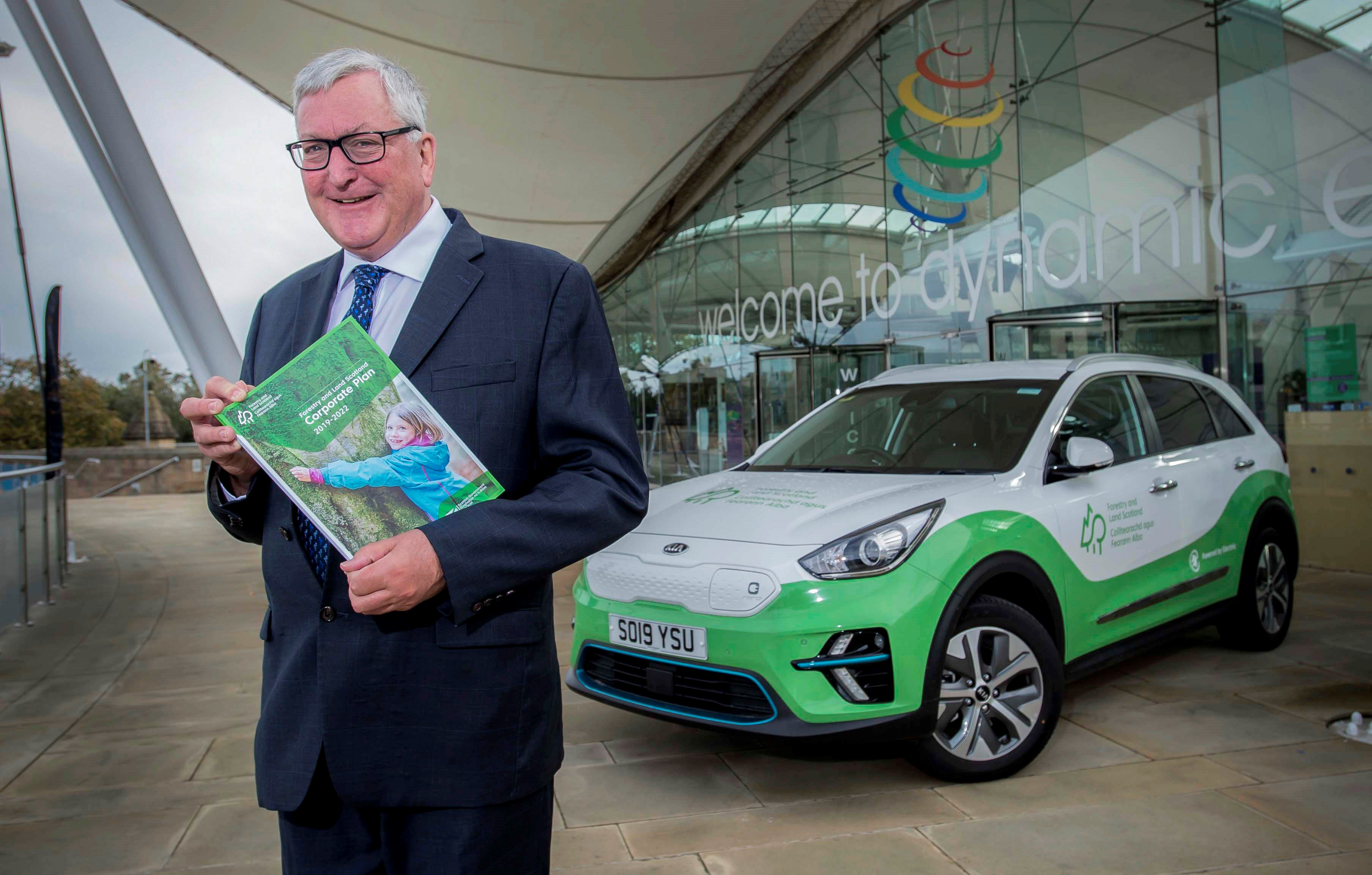 Fergus Ewing holding a copy of the Corporate Plan in front of an electric car