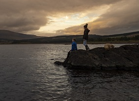 Two children by Clatteringshaws Loch at sunset