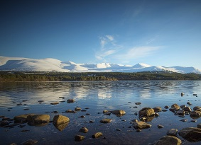 Loch Morlich with snowy hills in the background and rocks in the shallow water in the foreground