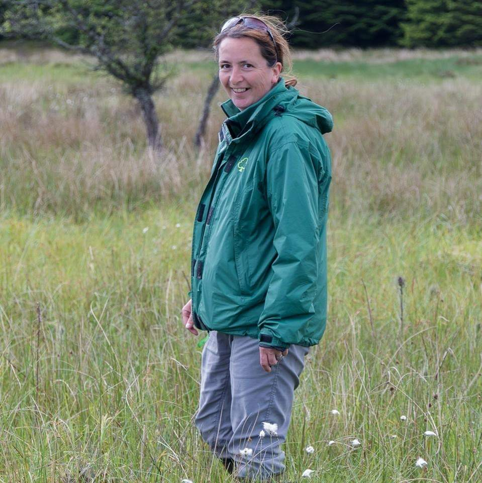 A female forestry worker standing in an open field.