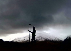 Silhouette of a person holding a measuring tool; a mountain in the background