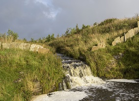 Small waterfall directed by stone flood defences
