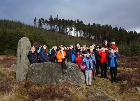 A large group of schoolchildren that appear to be looking at an eclipse while stood next to a large boulder