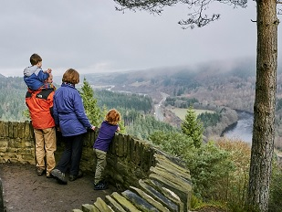 A family of four looking down on a forested glen from a viewpoint at Craigvinean