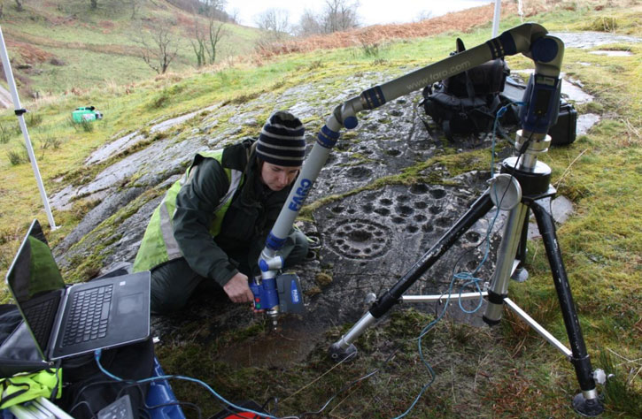 Archaeologist using a laser scanner on prehistoric rock art