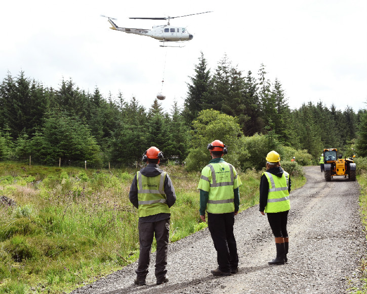 Helicoper flying in materials as three forestry workers watch