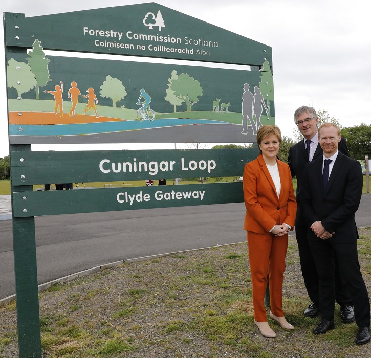 Two men and a woman standing beside a green sign for the Cuningar walking loop