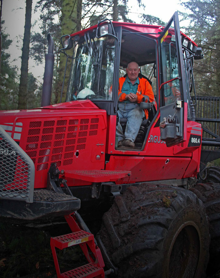 Grey haired old man in cab of a large forest machine smiling at camera