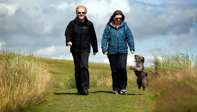 Two people walking a dog in the Kilpatrick Hills