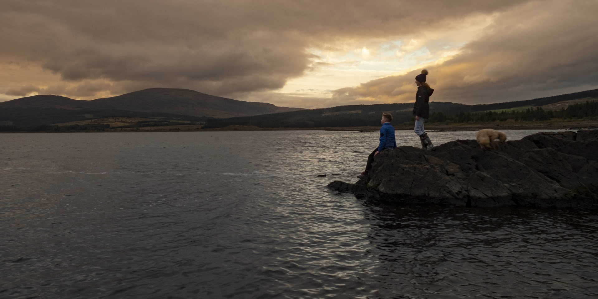 Image of man by loch at dusk