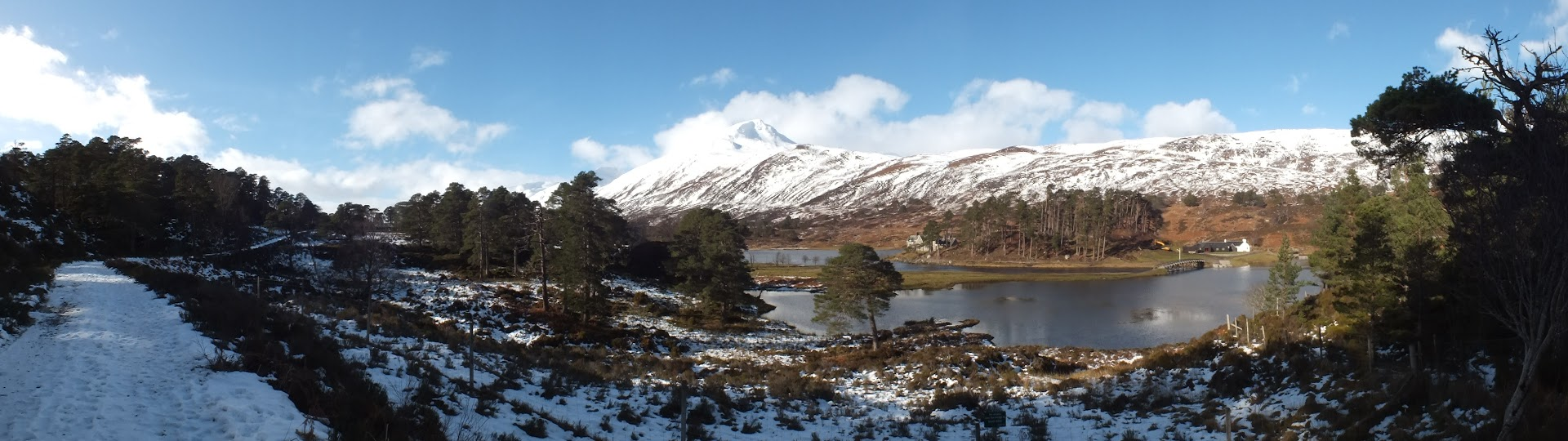 Panorama of a snow-covered woodland trail with a loch and mountains in the background