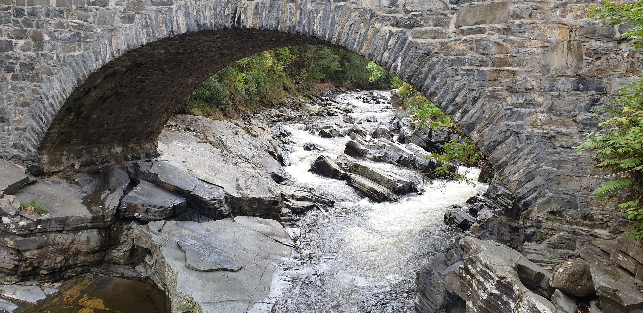 A stone, arched bridge over a narrow river
