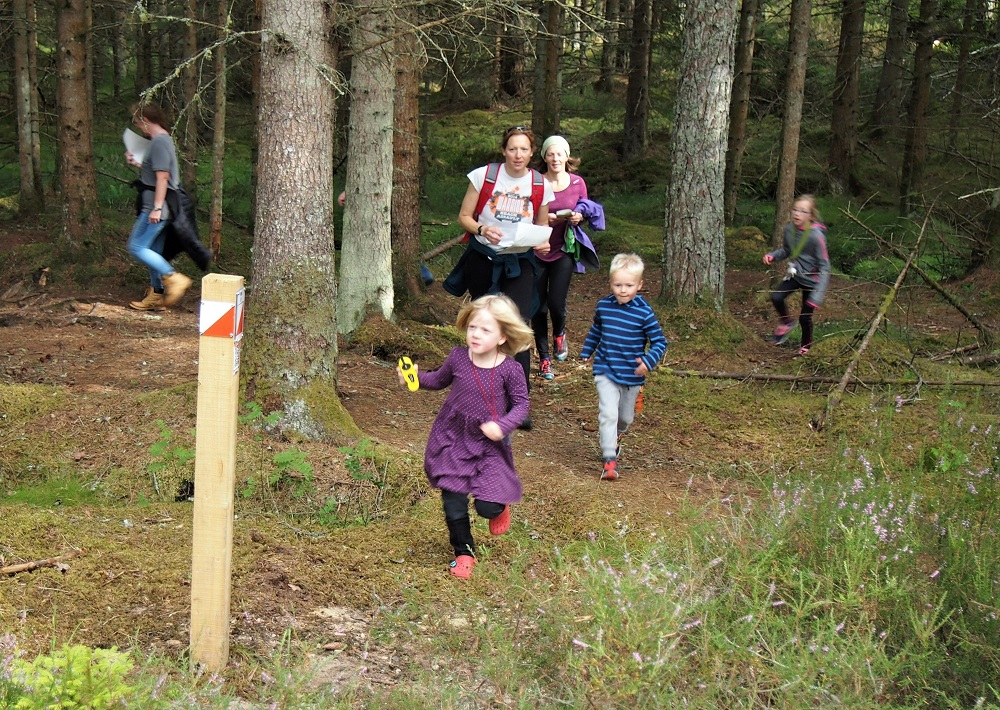 Two women follow a young girl and boy towards an orienteering marker post